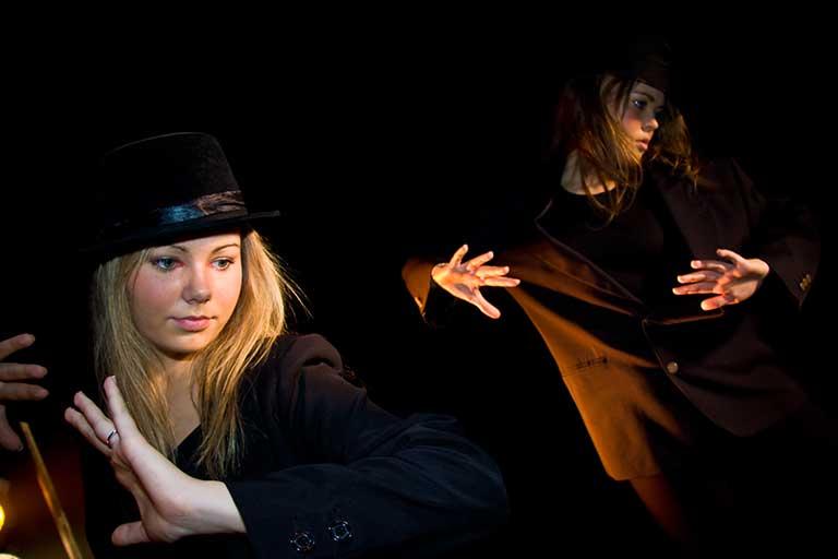 To piger danser i sort herretøj