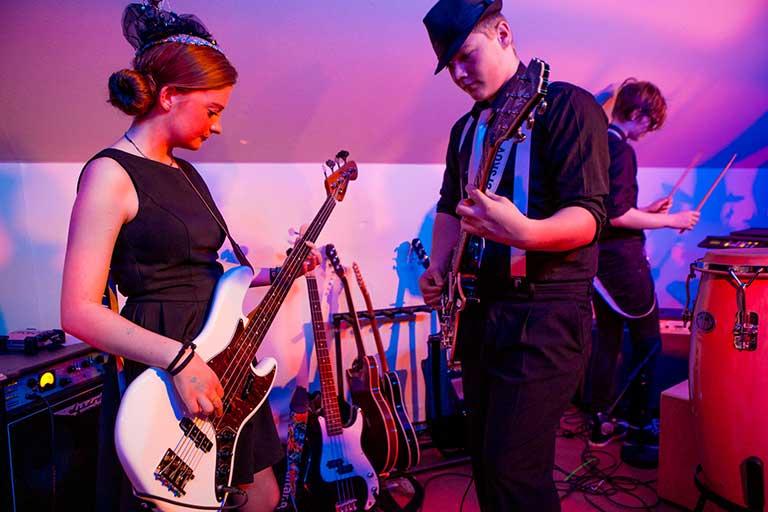 Elever spiller musik på elguitar til forestilling
