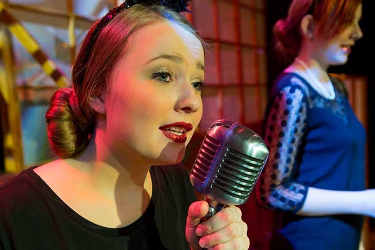 Musik-pige-synger-i-gammel-mikrofon-768