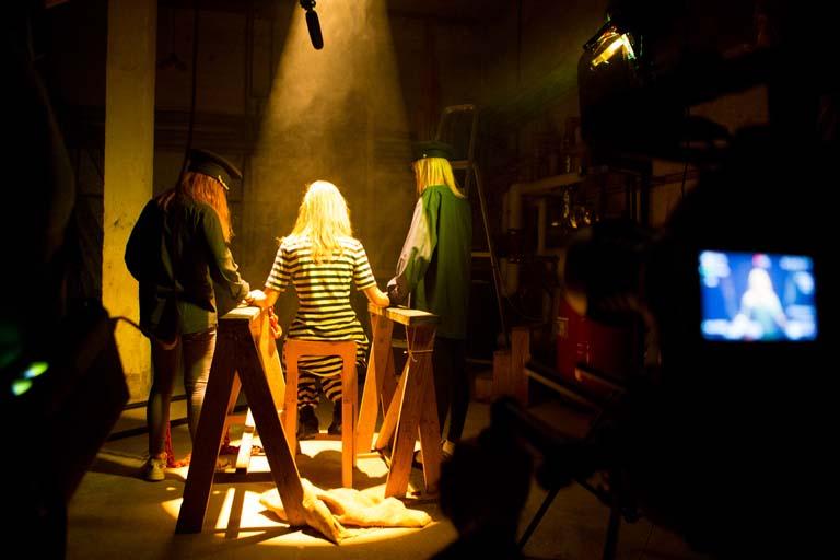 Billede fra filmoptagelse. En fange bliver spændt fast i en kælder