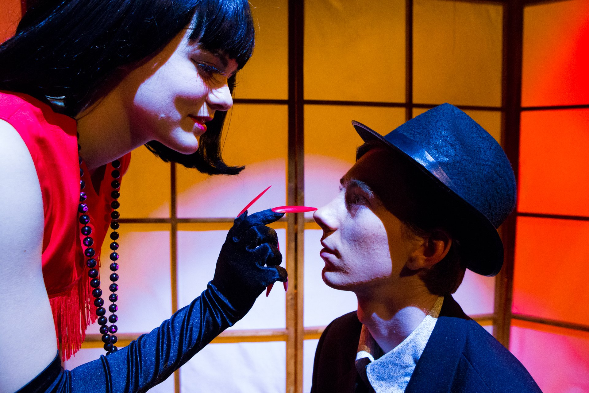 Teater stillfoto. Femme fatale med lange røde negle og paralyseret mand