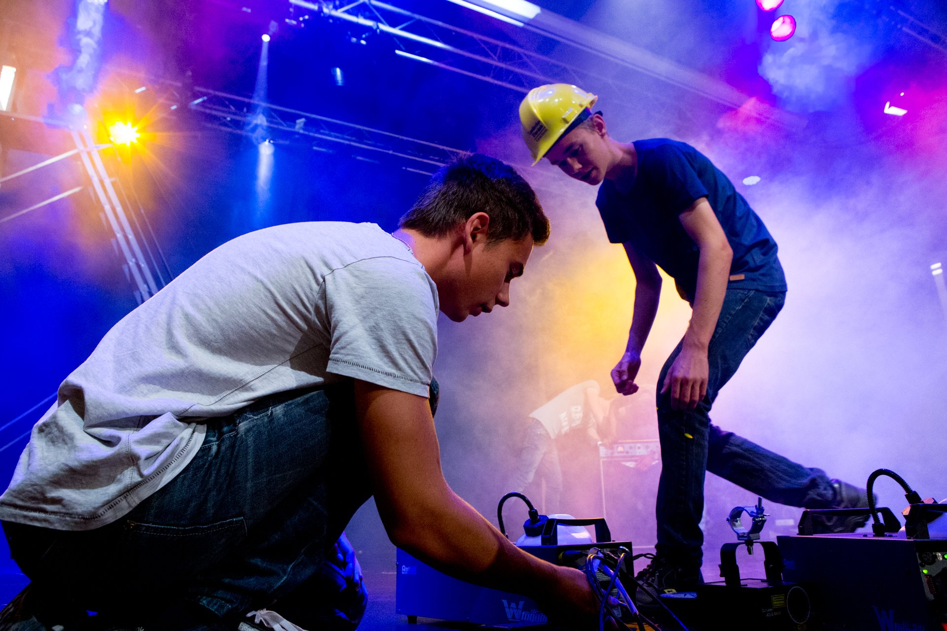 To drenge arbejder med sceneteknik i blåt lys og røg