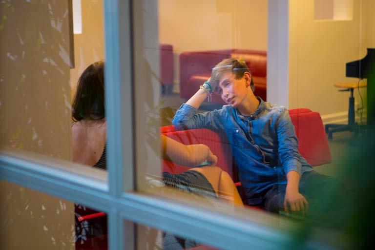 Dreng i samtale med pige på rød sofa