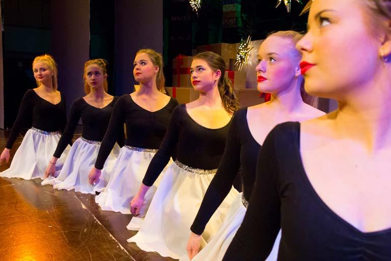 6 dansepiger på knæ i orange lys