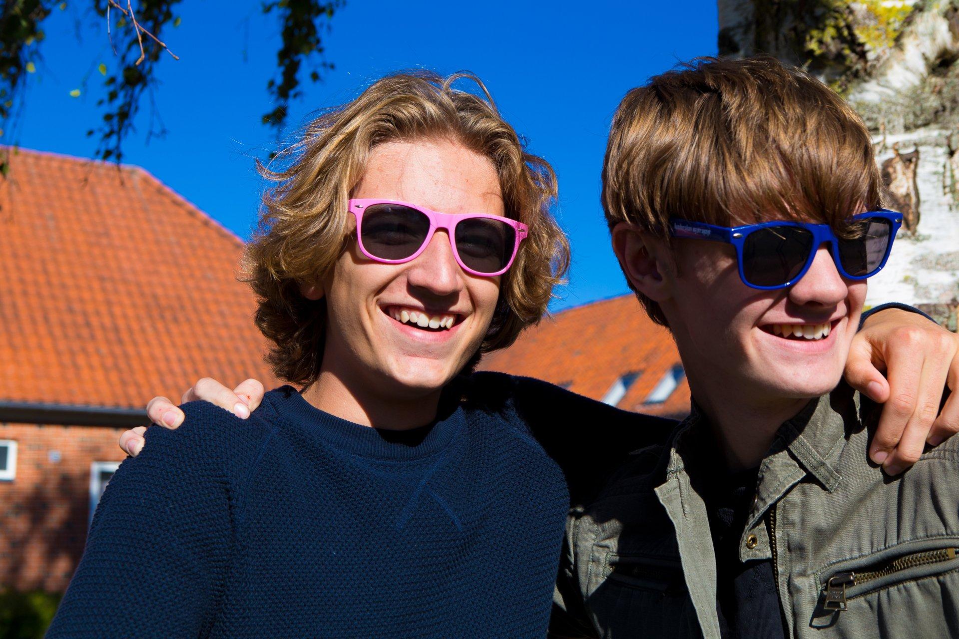To smilende drenge med solbriller